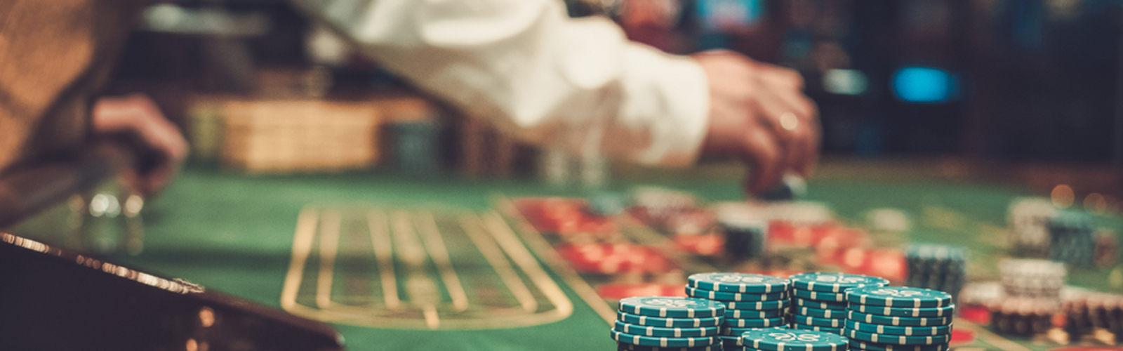 dealer with long sleeve distribute casino chips on roulette table